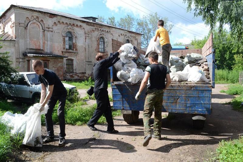 Погрузка мешков с мусором, на фоне еще непереданного собора XVI века