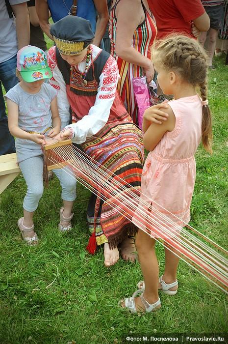 Маленьких гостей фестиваля учат ткать пояс на бердо