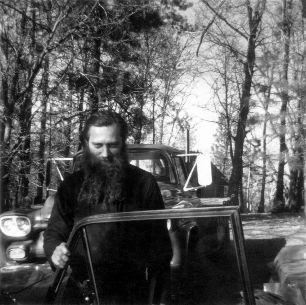 Евгений Роуз у монастырского грузовика. Позади виднеется печатная мастерская. 1969 г.