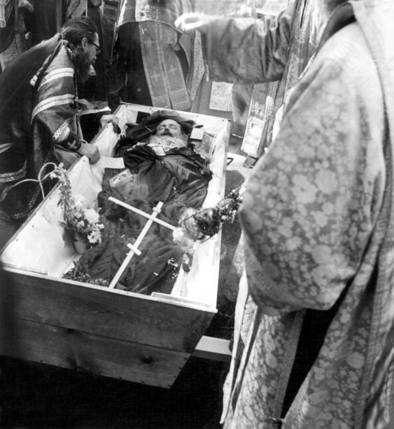 О. Герман прощается с усопшим. Через несколько мгновений гроб будет опущен в могилу