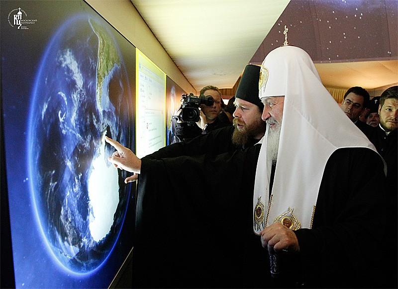 Патриарх у интерактивного глобуса на выставке