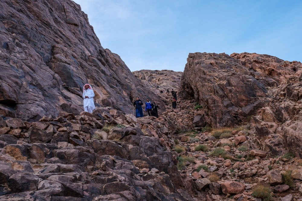 Pilgrims, led by a bedouin, are walking down the mountain