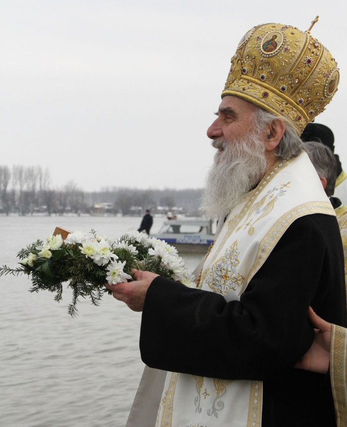 Patriarch Irinej of Serbia is throwing the cross in the water.
