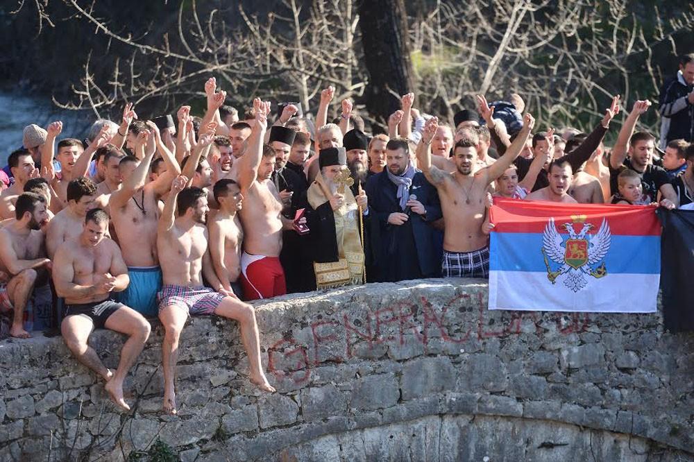 Metropolitan Amfilohije with participants in the swim in the Morac River.